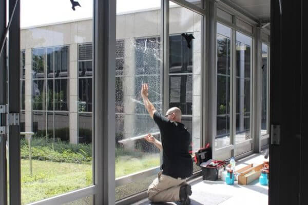 A man installing window film
