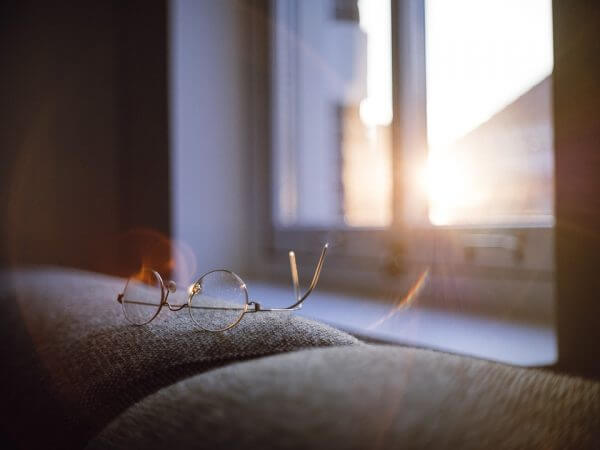 Glasses next to a window at sunrise