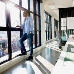 man standing by an office window
