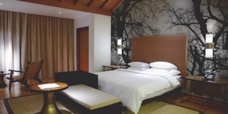 A bedroom with forest wall graphics