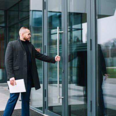a man touching a door handle as he opens a door